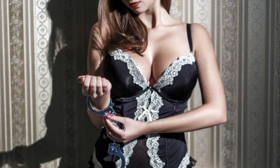 Sexy woman in corset locking handcuffs at vintage wall