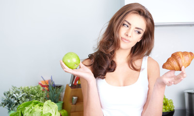35974574 - diet. dieting concept. healthy food. beautiful young woman choosing between fruits and sweets